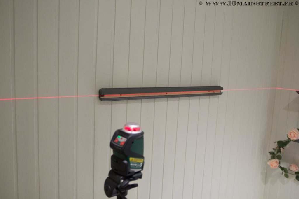 Mâchoire en bois fixée au mur pour accueillir la tablette à cadres