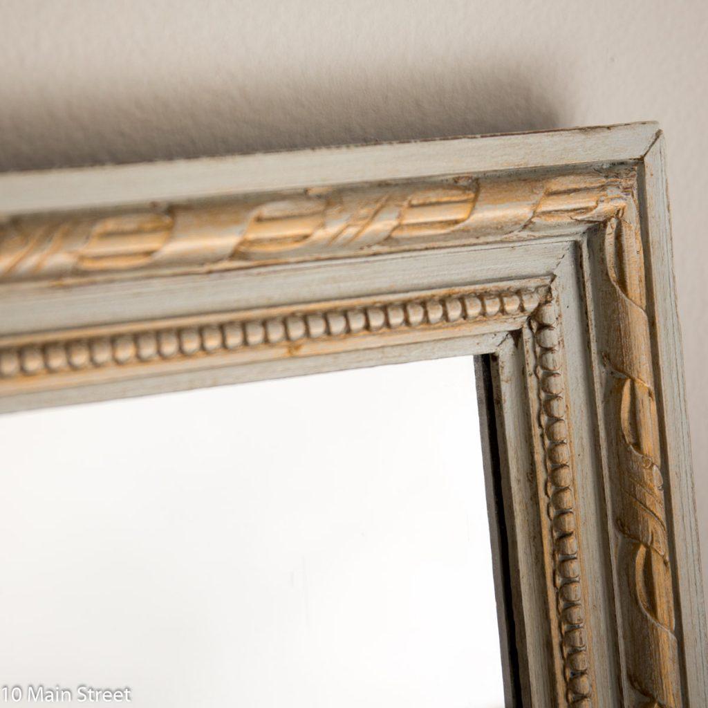 Détail du miroir patiné gris et or