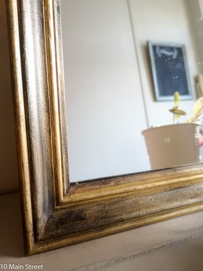 Détail du miroir patiné noir et or