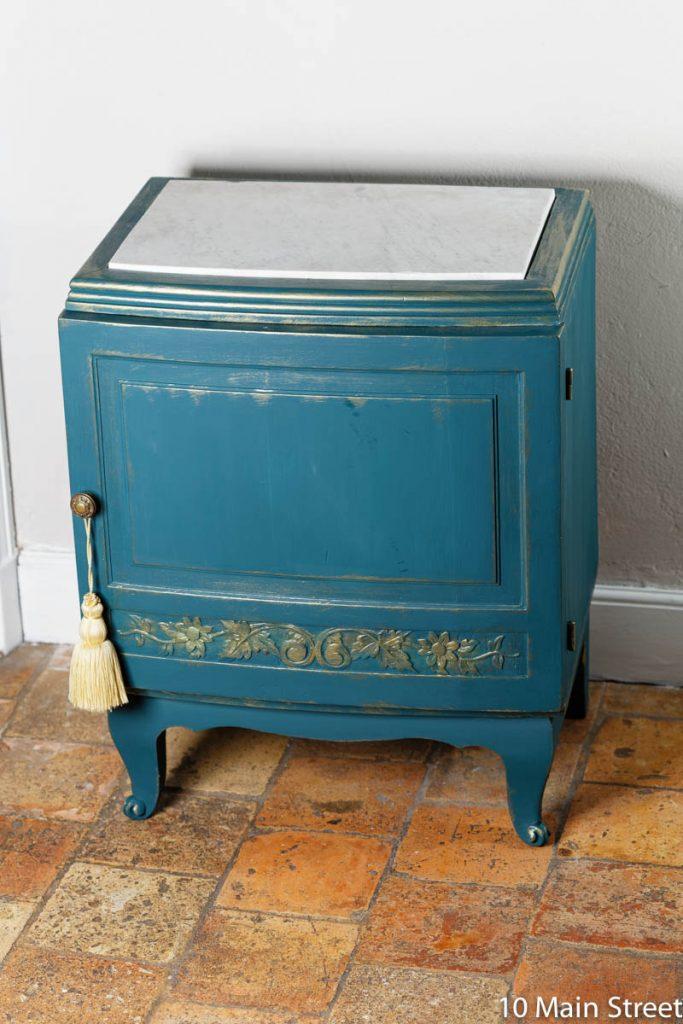 Le chevet aart-déco relooké en bleu pétrole avec son nouveau plateau en marbre