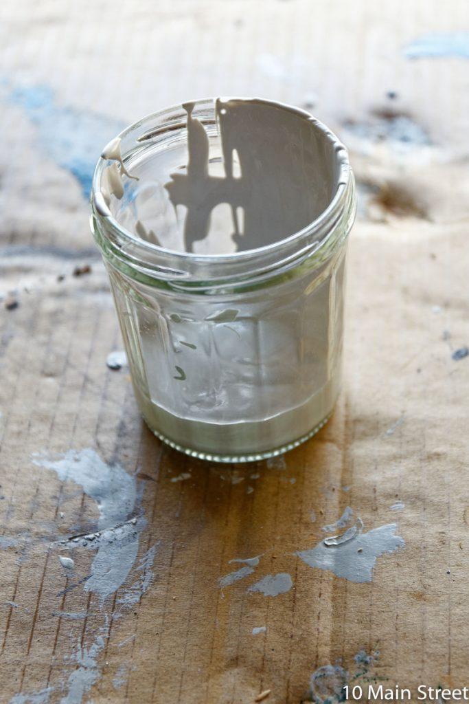 Reste de peinture blanche dans un pot de confiture