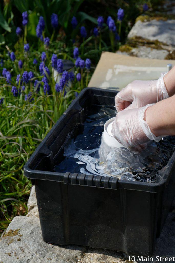 Cache-pot plongé dans le bain d'eau et de vernis à ongles