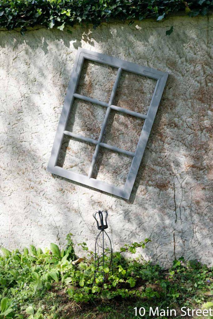 Vieille fenêtre utilisée comme treillis pour un hortensia grimpant