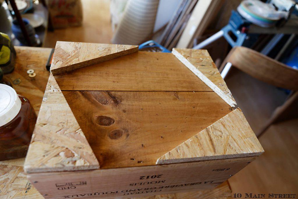 Chutes de bois fixées sous une caisse pour visser des roulettes